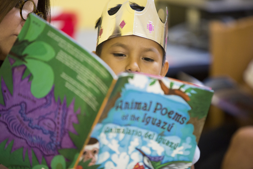 Child wearing golden crown while reading a book