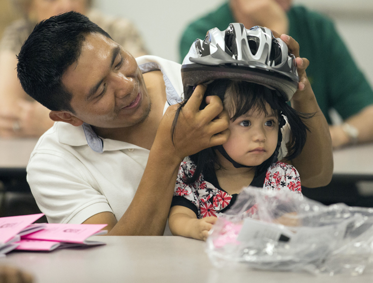 Dad fitting daughter with helmet