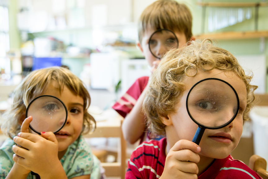 Children looking through magnifying glass