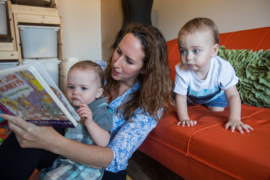 Mother reading to two young boys