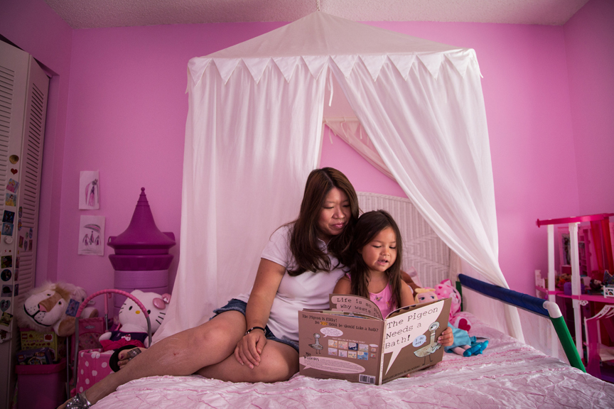 Daughter reading book to her mother