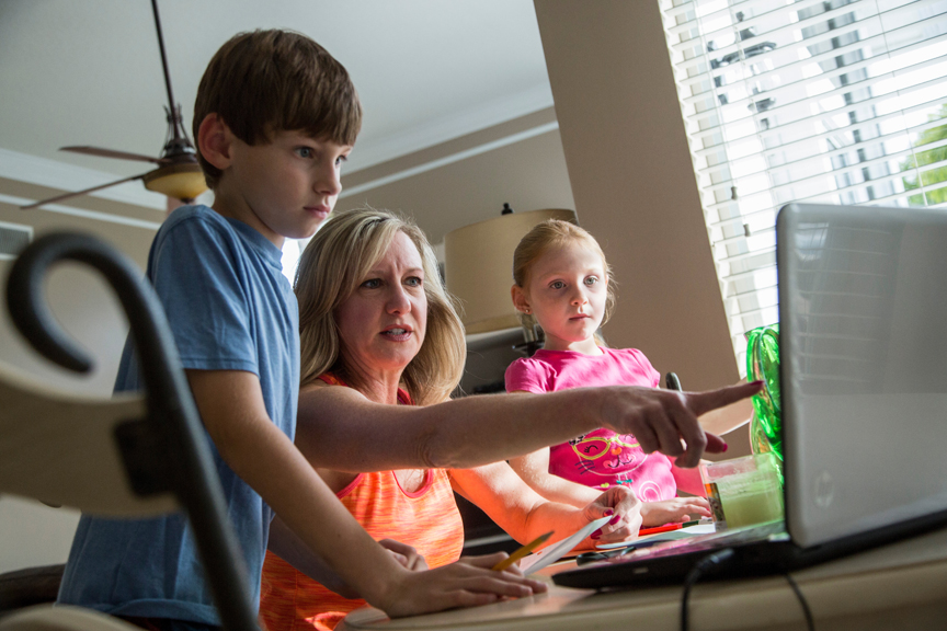 Mother showing son and daughter something on the computer