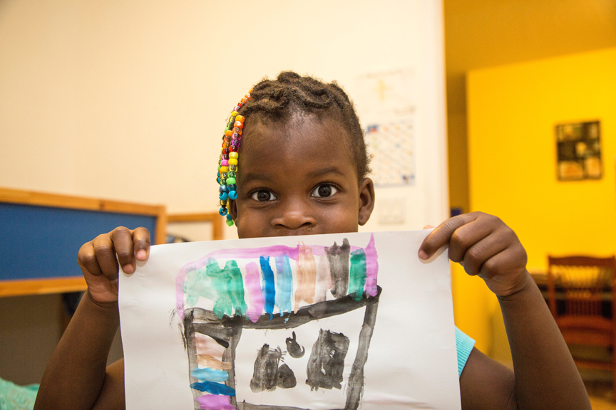 Young girl holding up her drawing