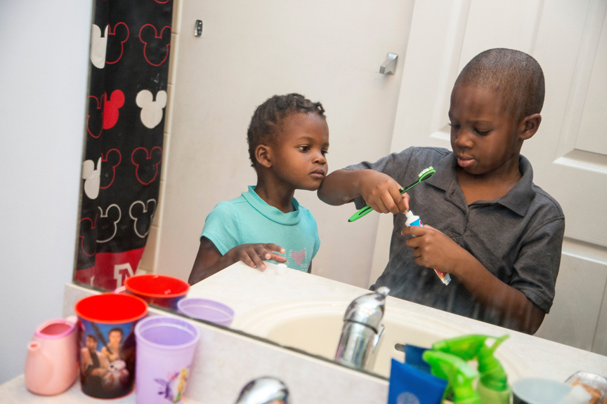 Young boy and young girl brushing their teeth