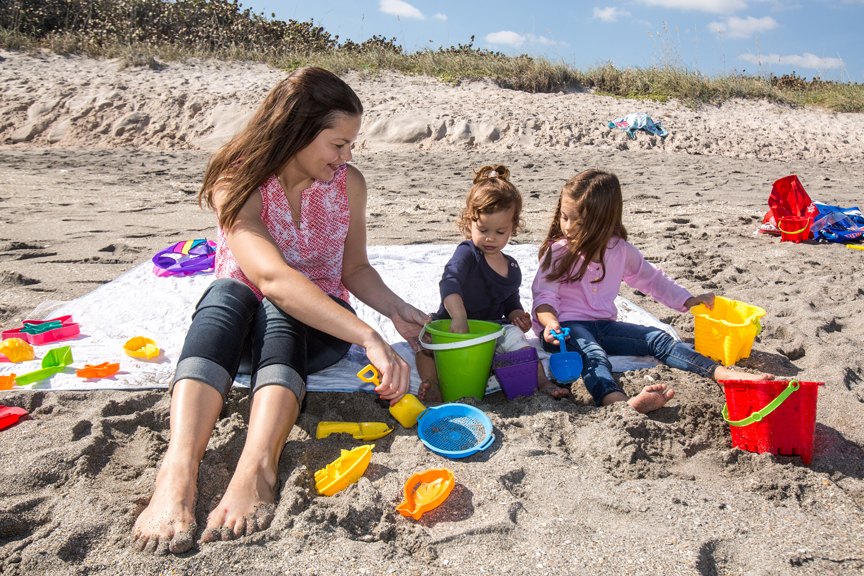 Mother and two daughters on the beach playing in the sand