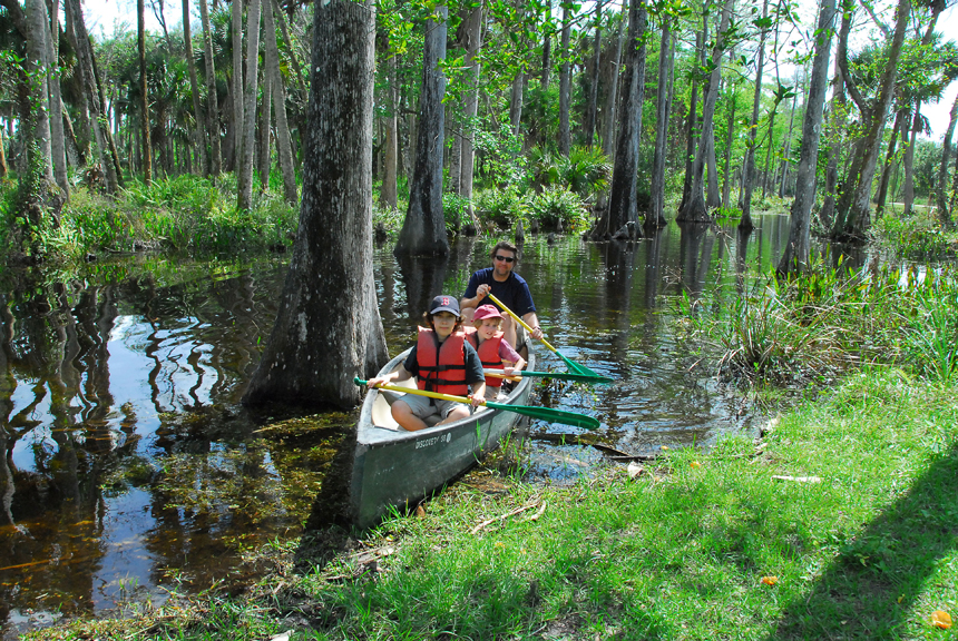 Man and young children in canoe
