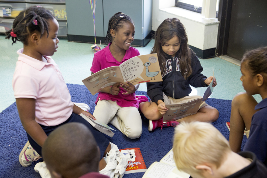 Children reading books to each other