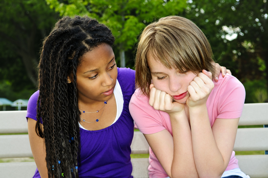 Teenage girls consoling one another