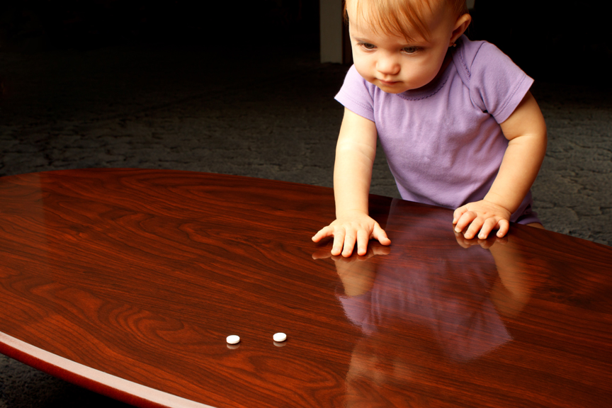 Young girl reaching for pills left on table