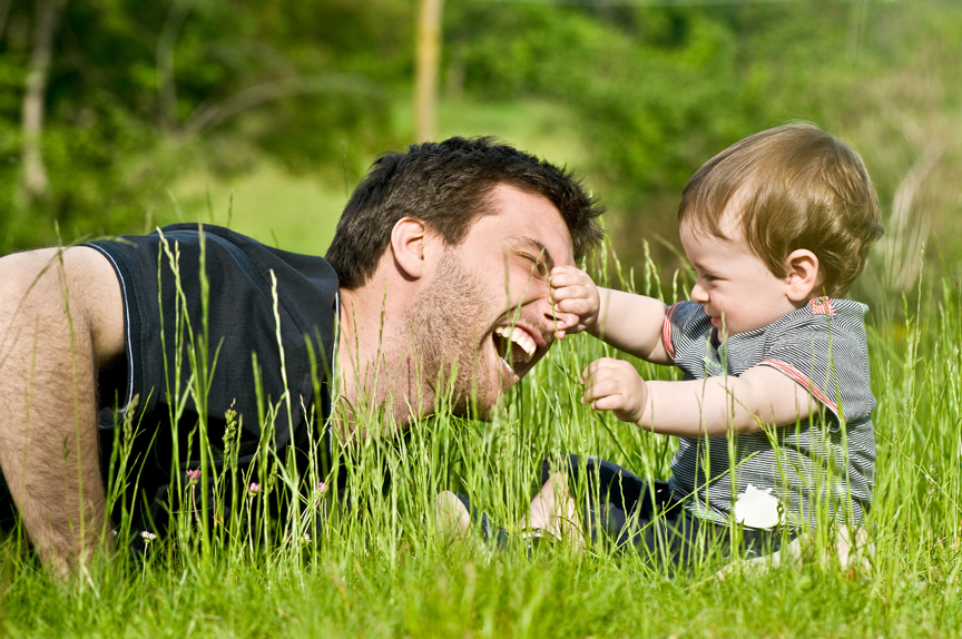 Father and young son playing in field