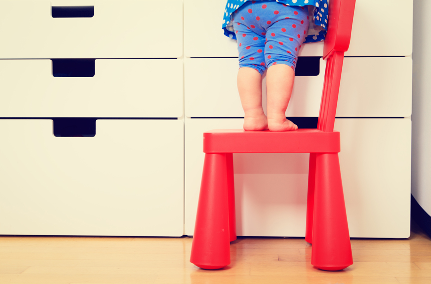 Young child standing on chair to get to countertop