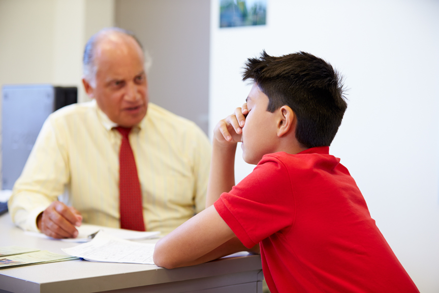 Boy looking stressed while talking with adult