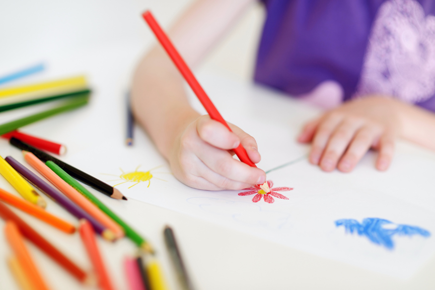 Child drawing flowers with colored pencils