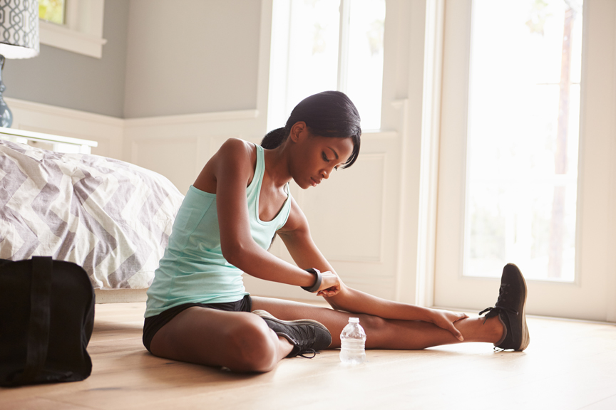 Woman stretching looking at fitness watch