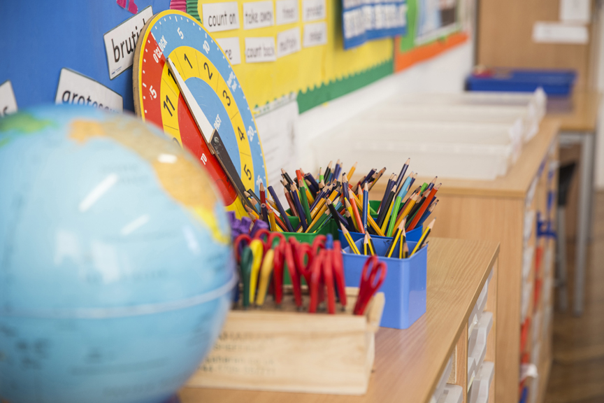 Classroom supplies including globe, scissors and colored pencils