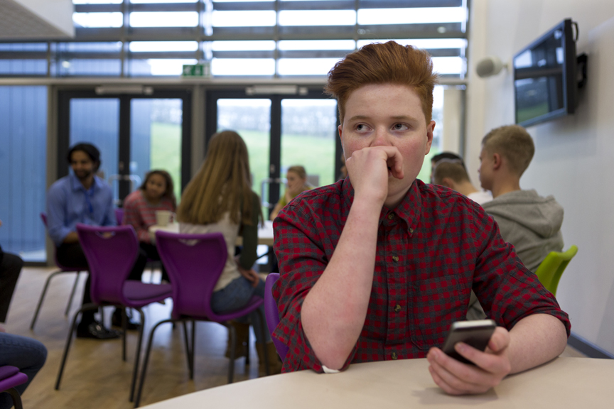 Teenager looking concerned holding phone