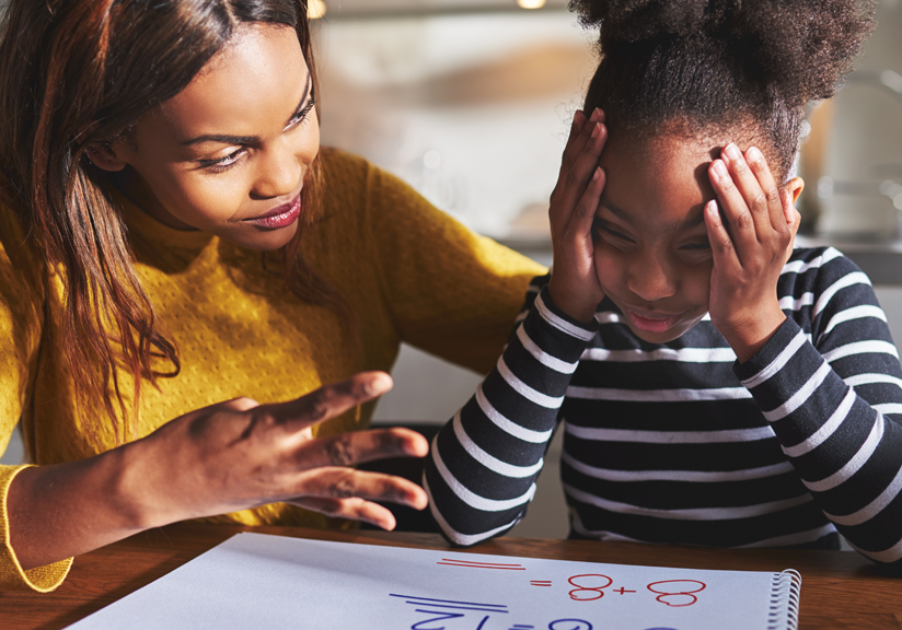Woman helping young girl with homework