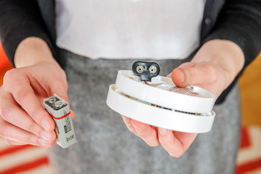 Person holding smoke alarm and battery