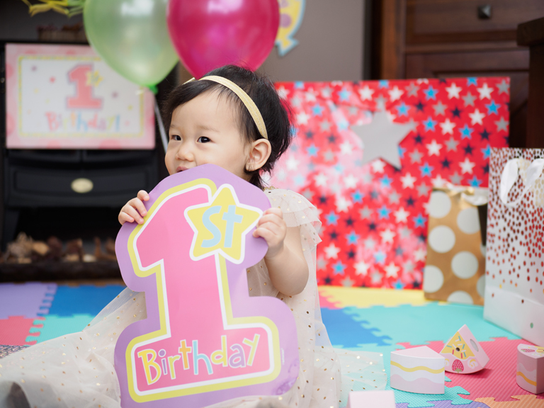 Young girl holding first birthday sign