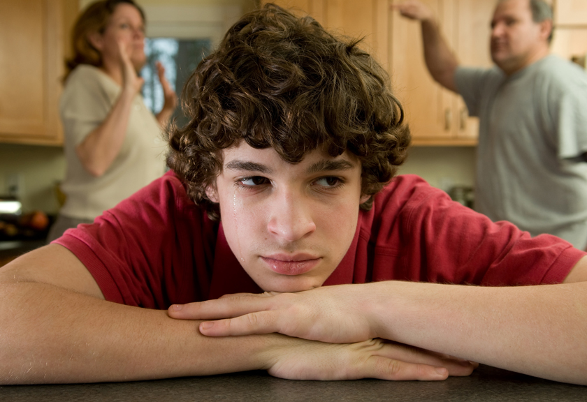 Teenager appearing sad while adults fight in the background