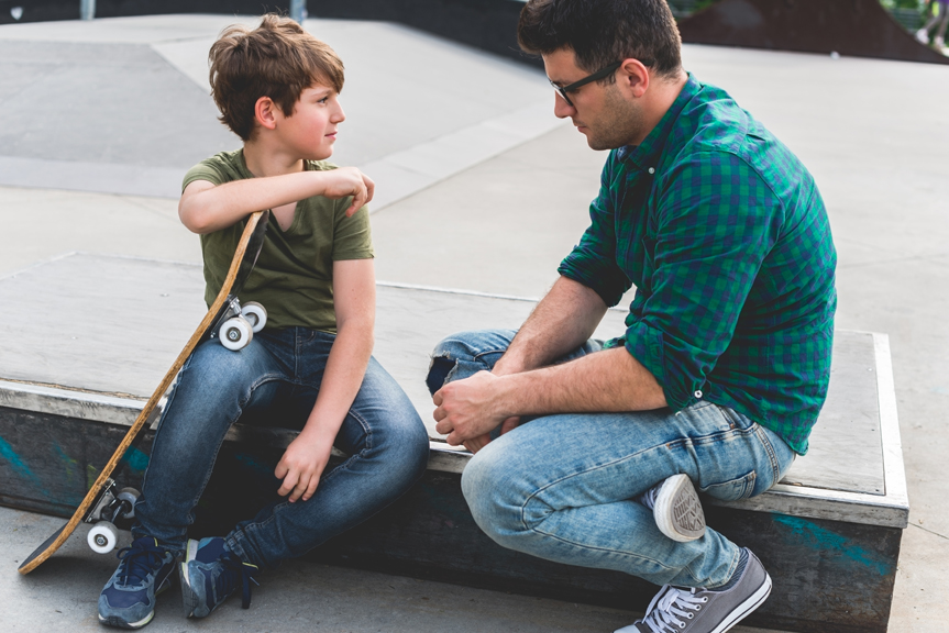 Father speaking with son at skateboard park