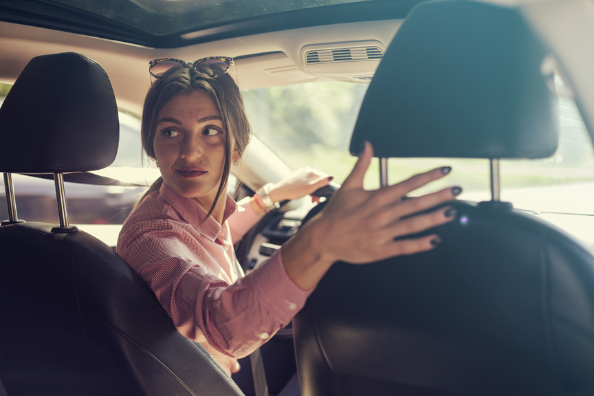 Women looking behind while backing up car