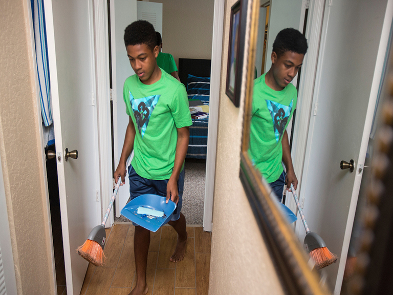 Teen boy walks down a hallway in his home with a broom and dustpan.
