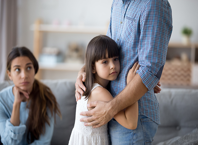 Sad little girl hugs father while mother watches from afar.