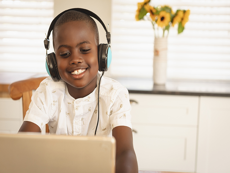 Boy smiling, with headphones in front of computer
